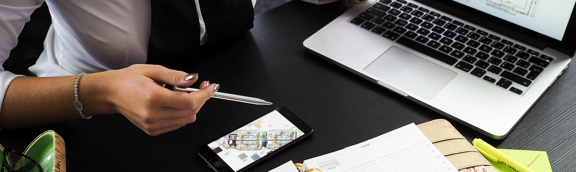 woman with pen and laptop looking at drawings